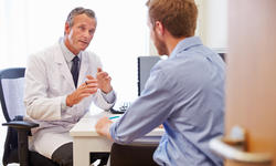 Male Patient Having Consultation With Doctor In Of